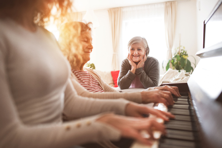 A girl with mother and grandmother playing the piano. Standard-Bild