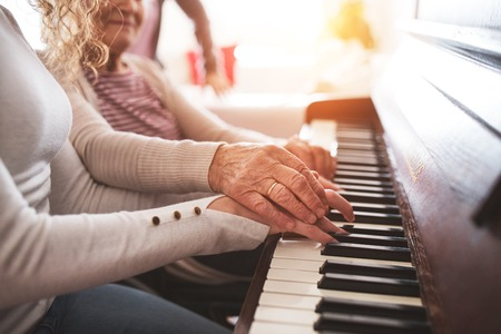 A girl with grandmother playing the piano. Stockfoto