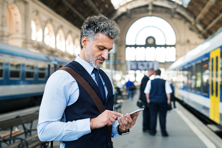 Mature businessman with smartphone on a train station. 스톡 콘텐츠