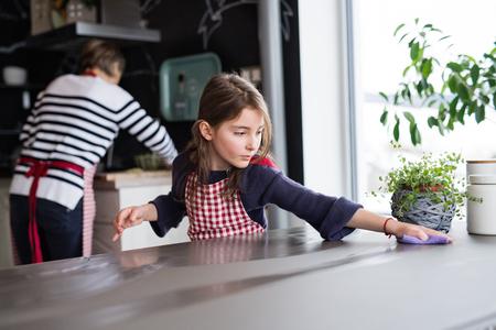家で祖母と一緒に料理をする小さな女の子。
