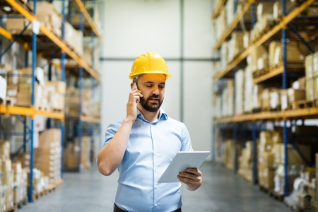 Warehouse worker or supervisor with a smartphone. 스톡 콘텐츠