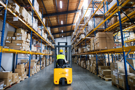 Warehouse man worker with forklift. Standard-Bild