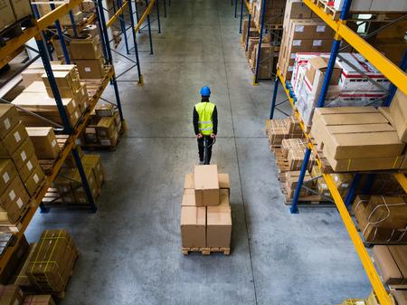 Male warehouse worker pulling a pallet truck.