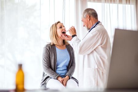 Lterer Doktor , der eine junge Frau im Büro überprüft Standard-Bild - 95543541