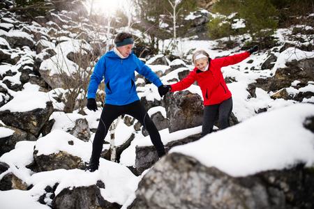 Senior couple jogging in winter nature.