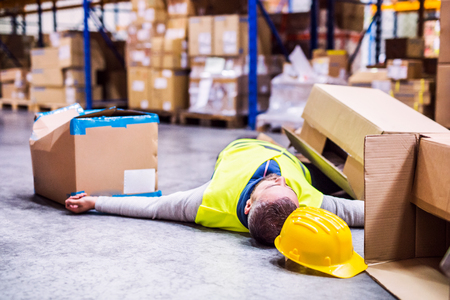 Warehouse worker after an accident in a warehouse. Archivio Fotografico