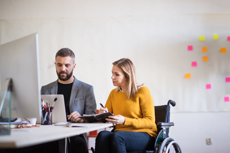 Two business people with wheelchair in the office. Archivio Fotografico