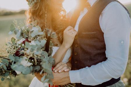 Mooie bruid en bruidegom bij zonsondergang in groene natuur.