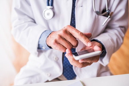 Senior doctor with smartphone working at the office.