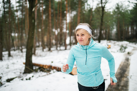 Senior woman jogging in winter nature. Stock Photo