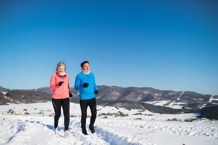 冬の自然の中でジョギングをするシニアカップル。