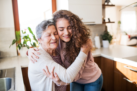 A teenage girl with grandmother at home, hugging. Stock fotó