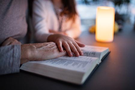 Ein kleines Mädchen und Großmutter lesen Bibel zu Hause