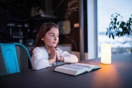 Een klein meisje dat thuis bidt. Stockfoto