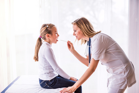 Young female doctor examining a small girl in her office. Фото со стока