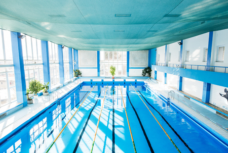 An interior of an indoor public swimming pool.