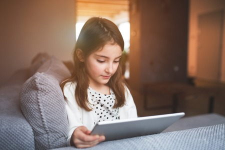 A small girl with tablet at home. Stock Photo