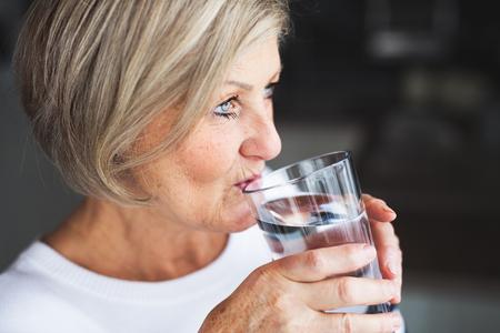 Senior woman drinking water in the kitchen.