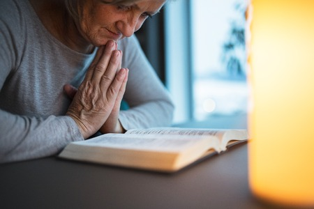 A senior woman praying at home.