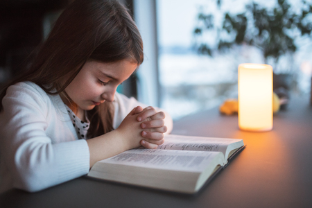 A small girl praying at home. Stockfoto