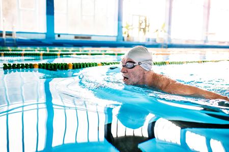Senior homme nageant dans une piscine couverte. Banque d'images