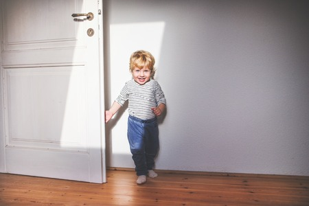 Cute toddler boy standing in a bedroom.