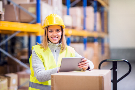 Woman warehouse worker with tablet. 스톡 콘텐츠
