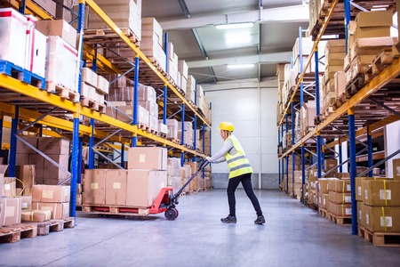 Woman warehouse worker with hand forklift truck. Banco de Imagens