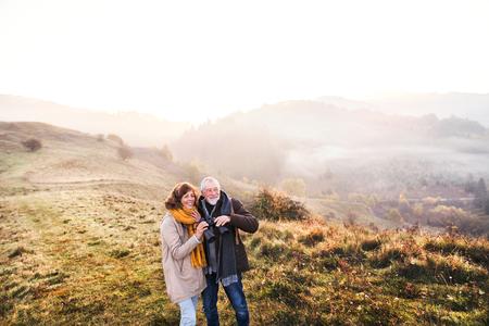Senior couple on a walk in an autumn nature. 版權商用圖片