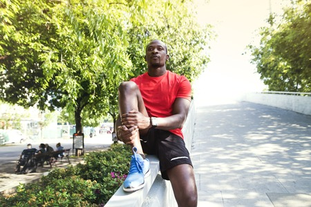Afro-american runner in the city resting.
