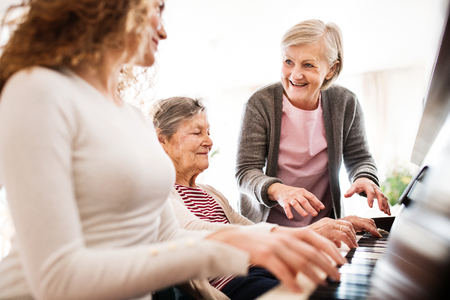 A girl with mother and grandmother playing the piano. Banque d'images