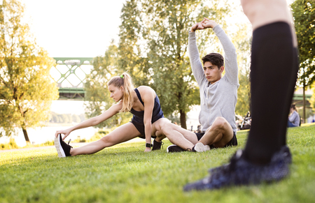 Young runners stretching and warming up in park. Stock Photo