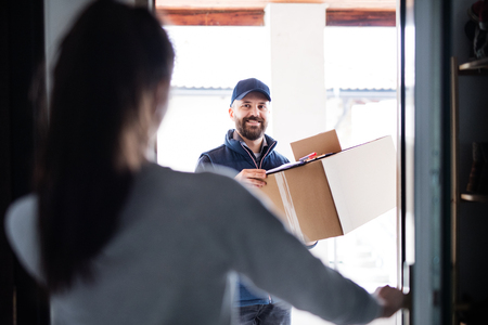 Woman receiving parcel from delivery man at the door. Banque d'images