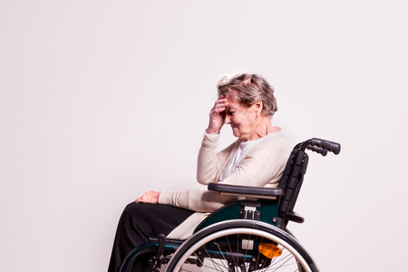 Portrait of an unhappy senior woman with wheelchair in studio. Imagens