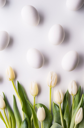 Flowers and white eggs on a white background. Flat lay. Stock fotó