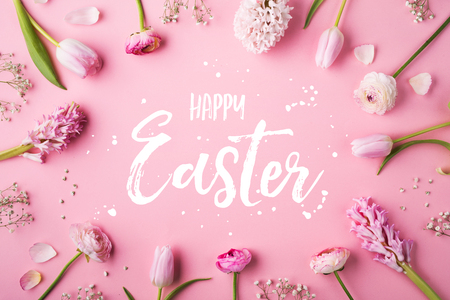 Happy Easter phrase and spring flat lay on a pink bacground. 스톡 콘텐츠