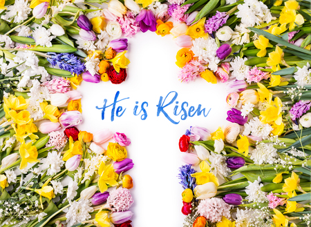 A cross on a colorful flower background. Easter flat lay.