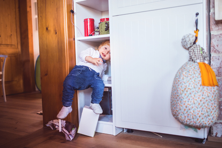 Toddler boy in dangerous situation at home. Child safety concept.