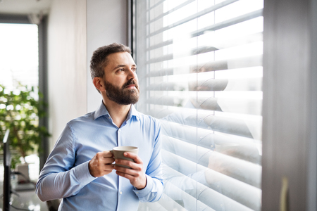 un homme par la fenêtre tenant une tasse de nuages. parc intelligent