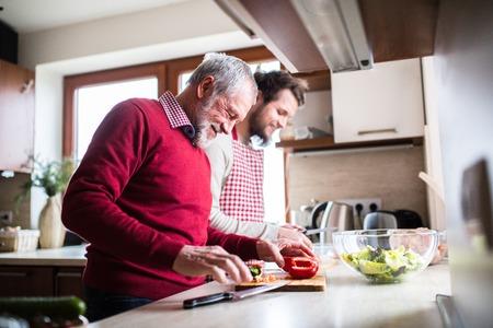 Hipster Sohn mit seinem älteren Vater in der Küche kochen Standard-Bild
