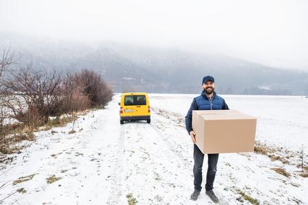 Delivery man delivering parcel box to recipient.