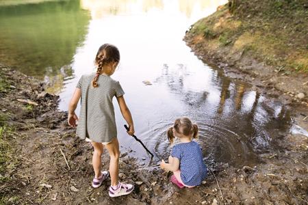 Little girls standing in the lake. Sunny summer.