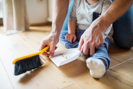 Unrecognizable father and toddler with brush and dustpan. Stok Fotoğraf