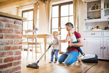 Father and two toddlers doing housework.