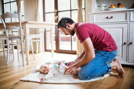 Father changing a baby girl at home.