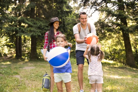 Beautiful young family with daughters going camping in forest. Banco de Imagens
