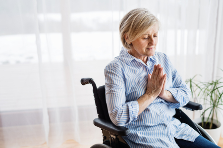 A senior woman in wheelchair praying at home. Stock Photo