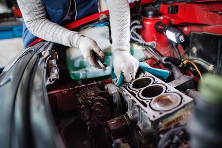 Mannmechaniker, der ein Auto in einer Garage repariert.