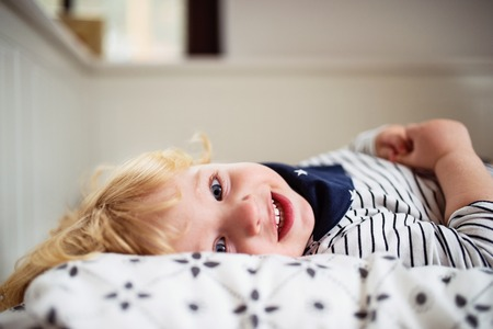 Cute toddler boy lying on the bed.