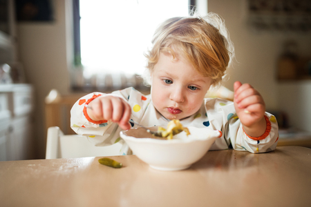 A toddler boy eating at home.